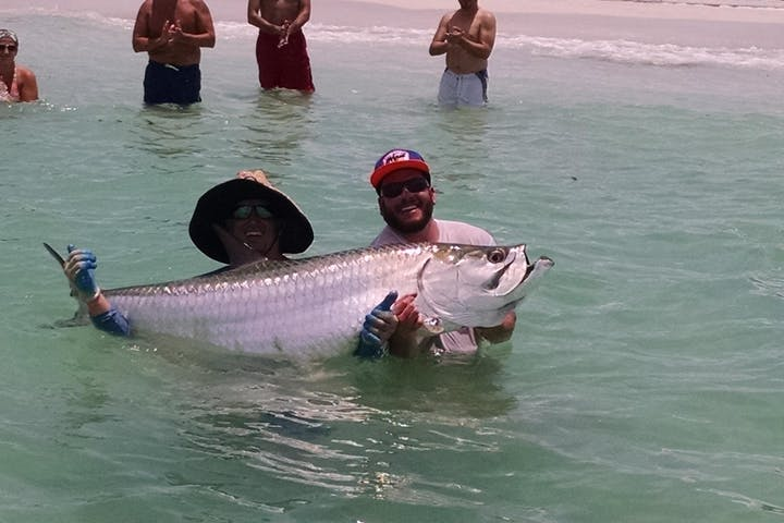 two men holding a tarpon out of the water in tampa