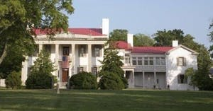 a large brick building with grass in front of a house with Belle Meade in the background