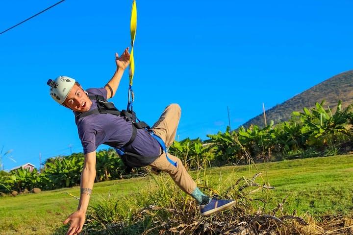 man zip lining across a farm in Maui