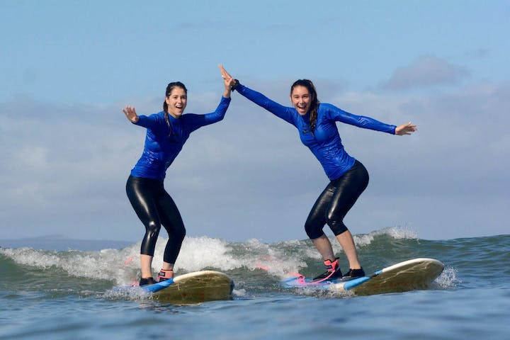 Girls surfing and high fiving