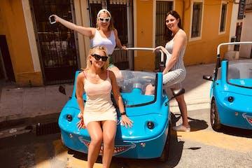 Trois femmes souriantes autour une NiceCar bleue