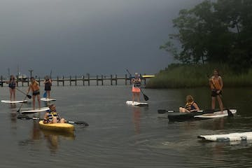 SUP riders and kayakers on an overcast day