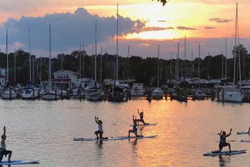 A group of people practicing yoga on the water at sunset