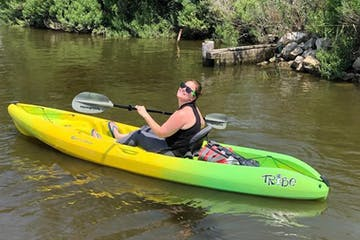 A happy visitor in a single person kayak exploring