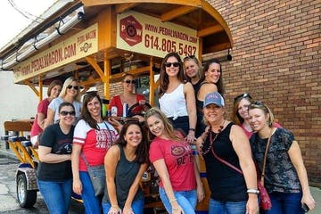 group of ladies taking photo in front of pedal wagon