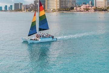 boat with rainbow sail on water with city in background at daytime