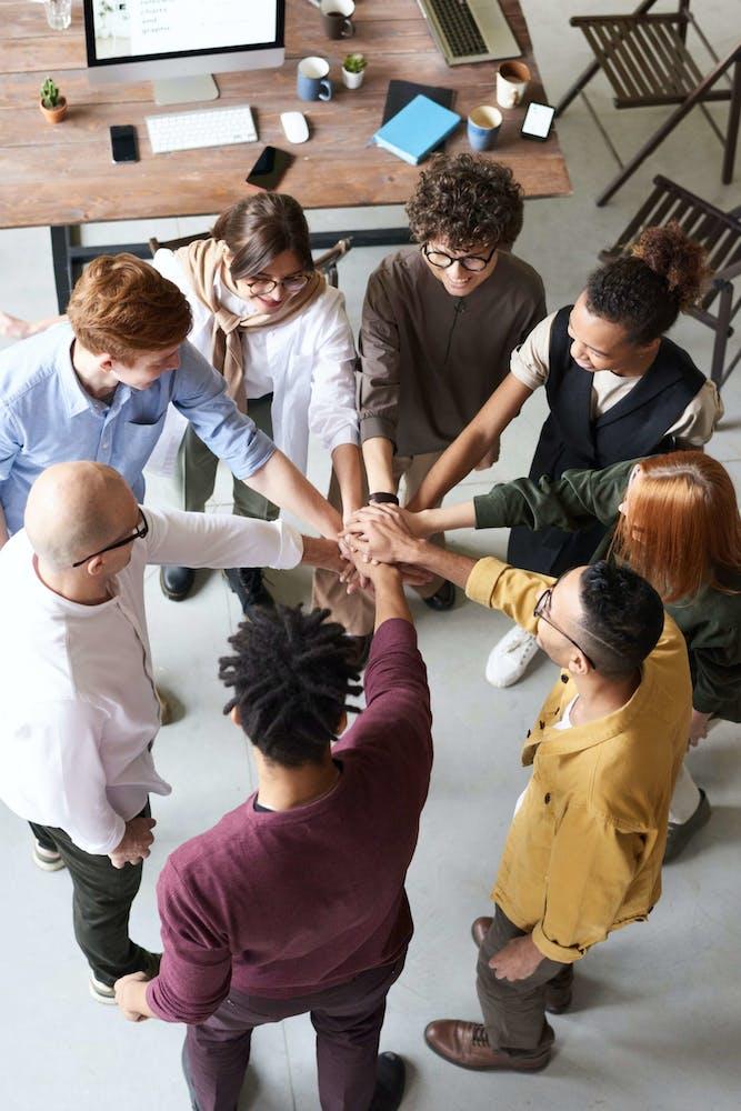Grupo de personas uniendo sus manos al centro de un círculo