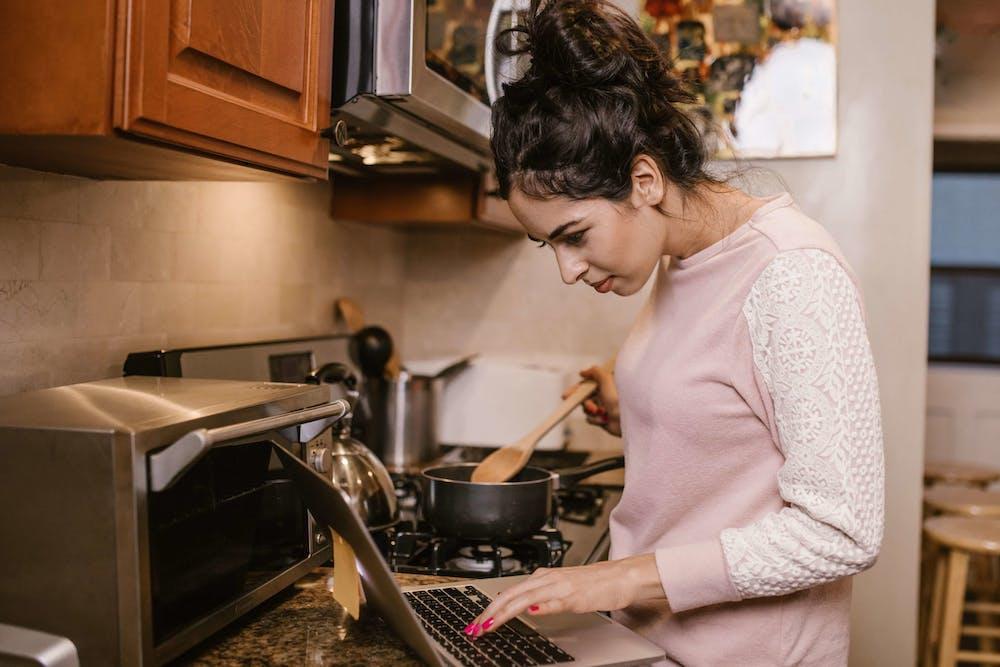 Mujer joven cocinando en su casa siguiendo las instrucciones desde su computadora