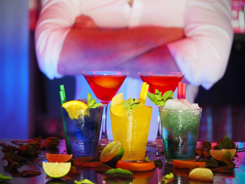Mixólogo con cuatro cócteles preparados sobre una barra
