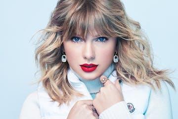 a close up of Taylor Swift wearing a blue shirt