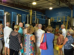 Group of tour participants listening to tour guide at Drum Circle Distillery