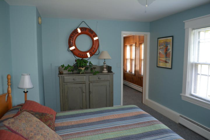 A bed, dresser & window in a room with blue walls