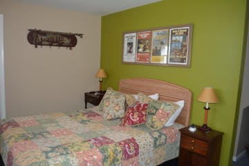 A bed in a room with a green wall with 4 pictures hanging