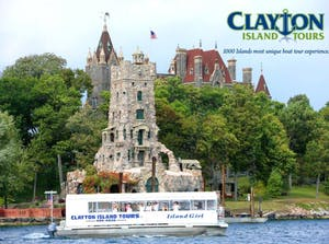 a white boat traveling down a river with Boldt Castle in the background