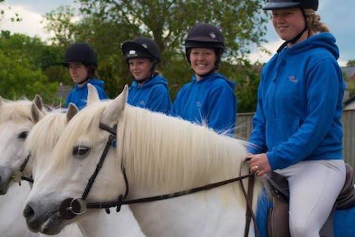 Four females sitting on four white horses