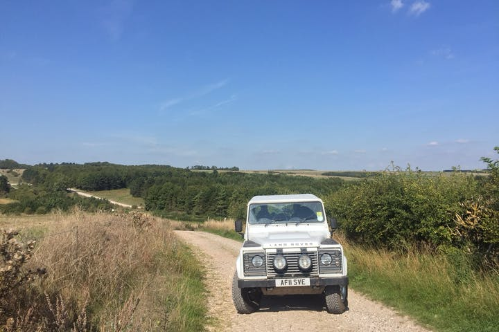 Picture of a white 4x4 Land Rover on a pathway next to a field