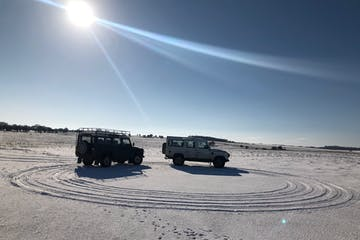 Two 4x4 Land Rovers on a snowy field