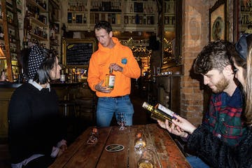 Tour guide speking about Irish whiskey in a pub.