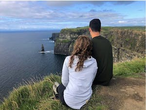 a couple sitting in front of the Cliffs of Moher