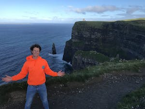 a man standing next to a body of water with Cliffs of Moher in the background