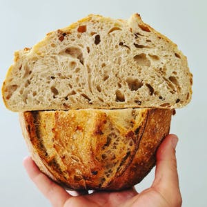 a hand holding a piece of bread