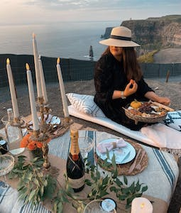 a woman sitting at a table with food and water