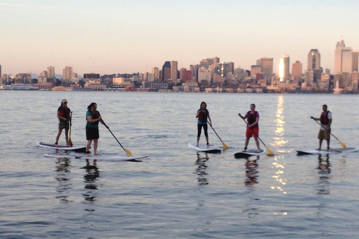 group of stand up paddle boarders in front of Seattle skyline
