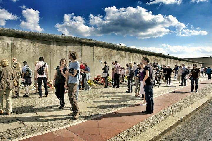 People hanging around Berlin's wall