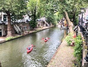 Twee mensen in een rode kano in een gracht