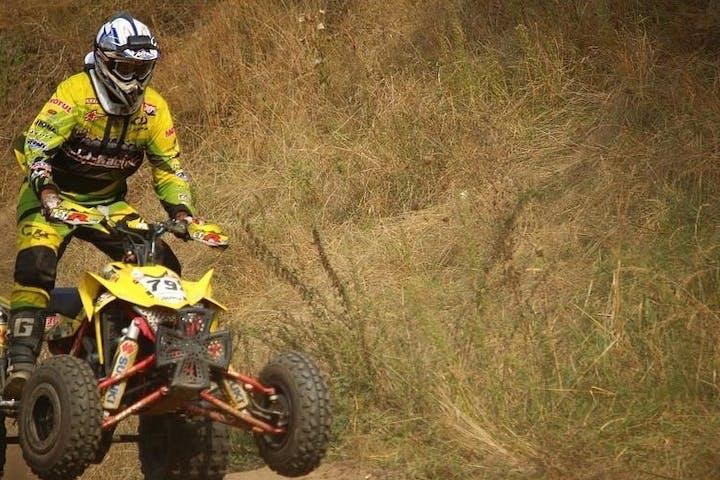 atv rider balancing on a jump