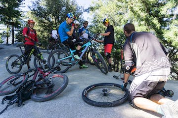 Group of mountain bikers working on bikes and setup before their rid
