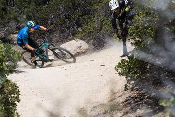 Two bikers riding down sandy mountain biking trail