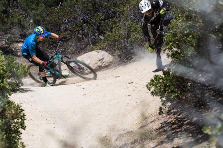 Two bikers riding down sandy mountain biking trail
