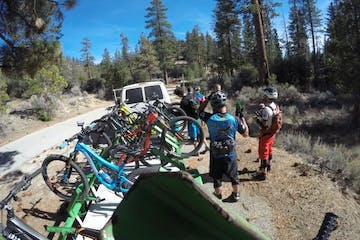 view of bike shuttle and bus parked next to trail head with bikers standing around