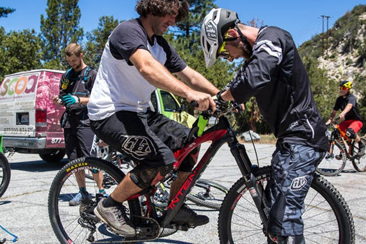 Guide helping biker adjust controls on his bike