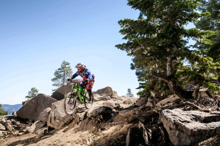 mountain biker catching air while riding on downhill trail