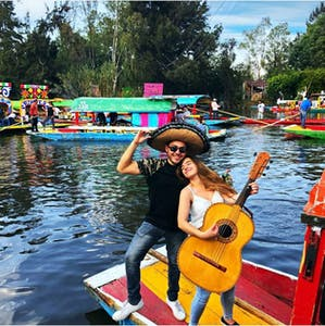 a group of people on a boat in the water with Xochimilco in the background