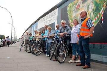 Gruppenfoto von einer Tour-Gruppe neben ihren Fahrrädern an der Berliner Mauer