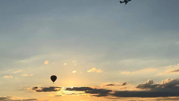 hot air balloons flying at sunset