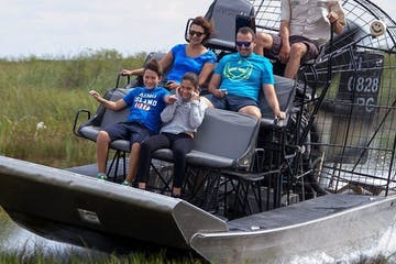 people riding an airboat in the florida everglades