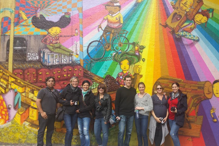 group posing in front of graffiti piece on wall