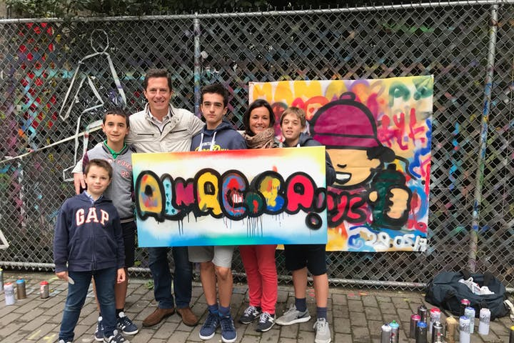 family standing with graffiti canvas