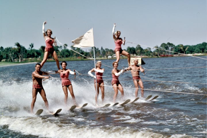 ski club members forming a pyramid while water skiing togehter