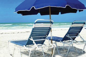 a couple of lawn chairs sitting on top of a sandy beach