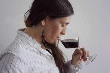 a person wearing glasses drinking from a glass