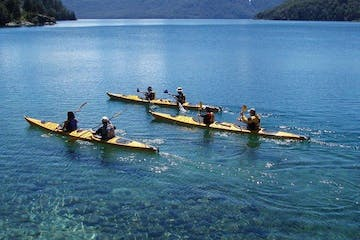 a group of people in a small boat in a body of water
