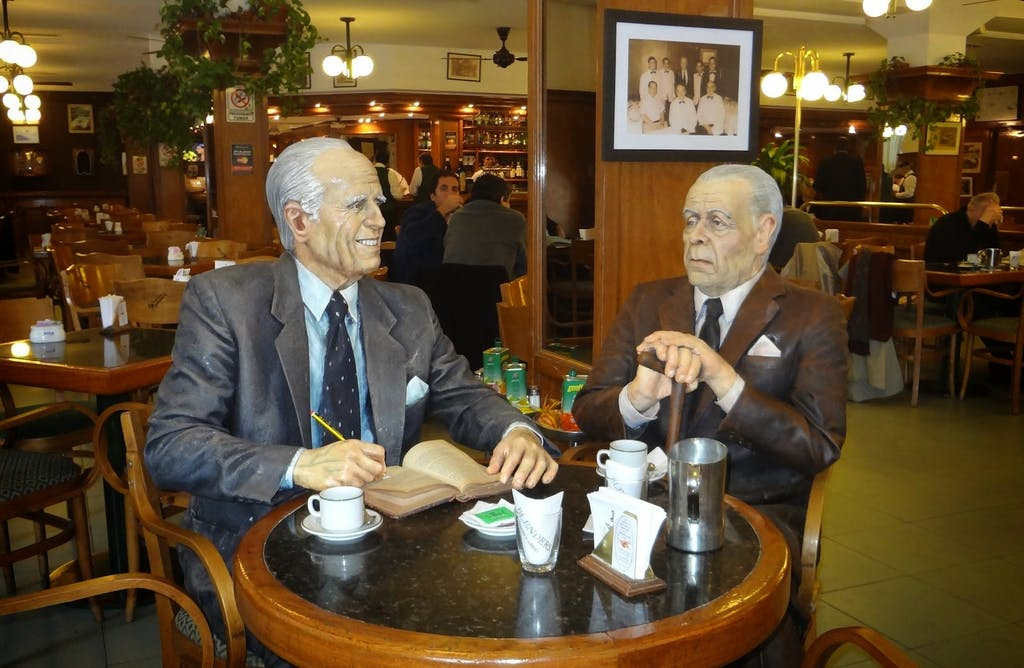 Borges and Bioy Casares (both writers)sitting at a table in a restaurant.