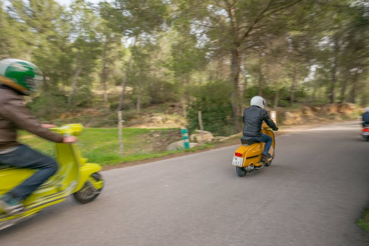 Men driving 2 vintage lambrettas