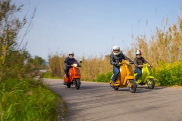 three men driving scooter trough Mallorca