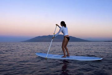 Woman on paddleboard at dusk
